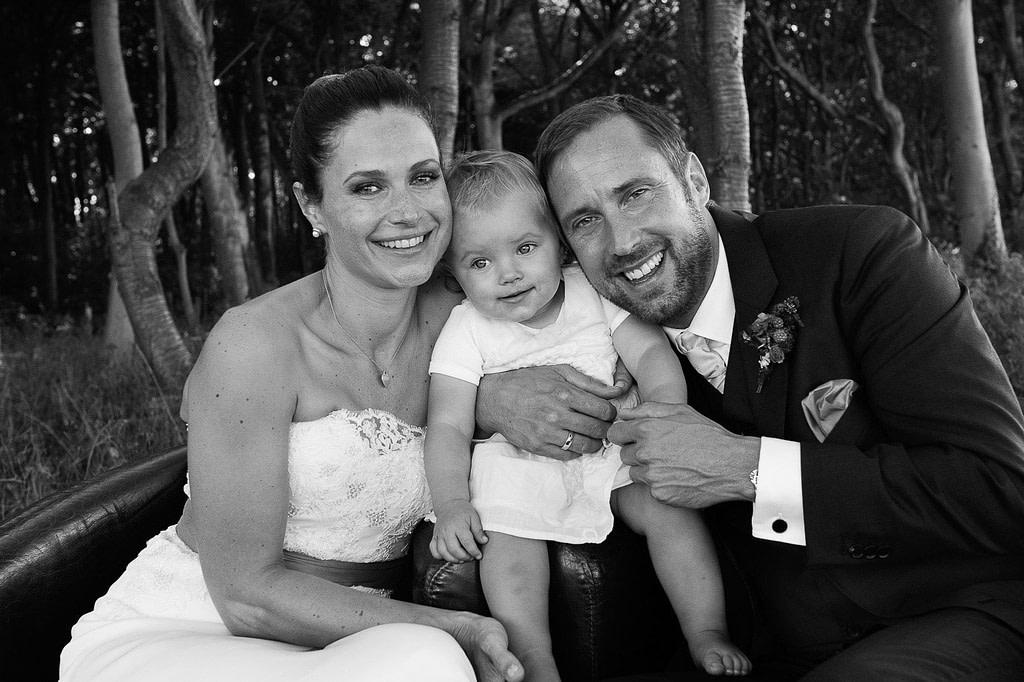 Hochzeitsfoto von braut und Bräutigam mit kleiner Tochter im Küstenwald vom Weissenhäuser Strand an der Ostsee beim Hochzeitsfotograf Hamburg