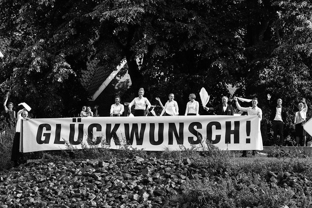 Die Mitarbeiter von Gerresheim serviert gratulieren dem Hochzeitspaar mit einem großen Banner an der Villa im Jachthafen bei Hochzeitsfotografie Hamburg