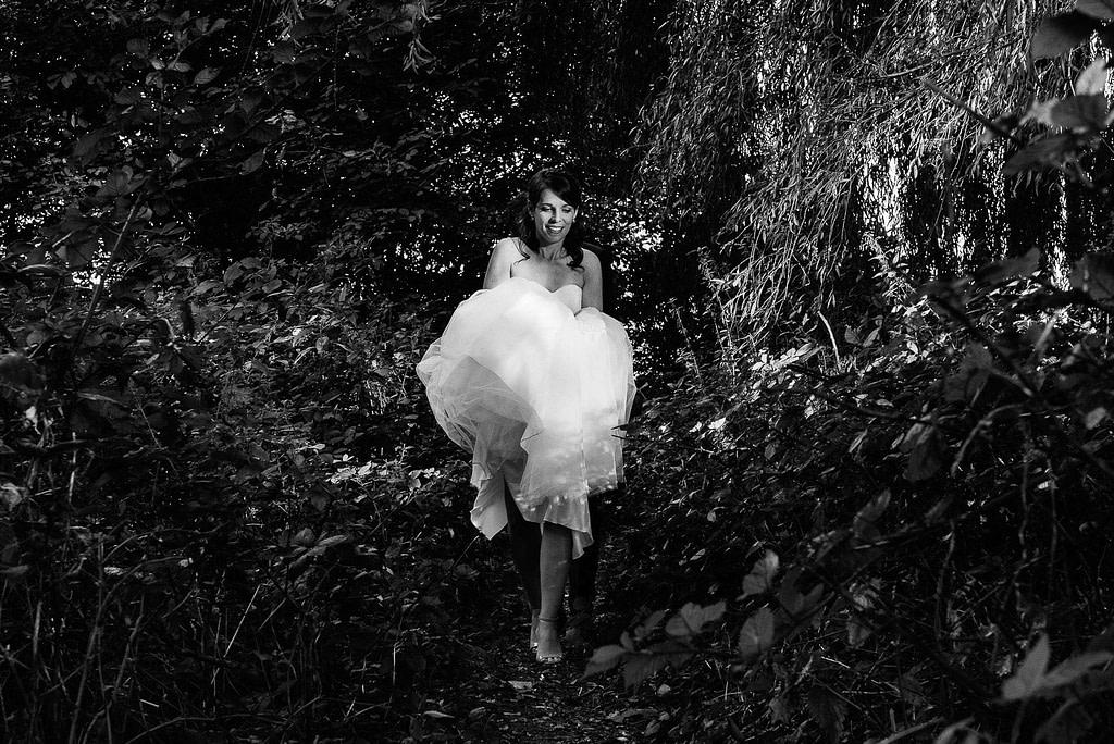 Die Braut steigt mit Ihrem Hochzeitskleid vorsichtig durch das Gestrüpp im Parkhafen bei Hochzeitsfotografie Hamburg
