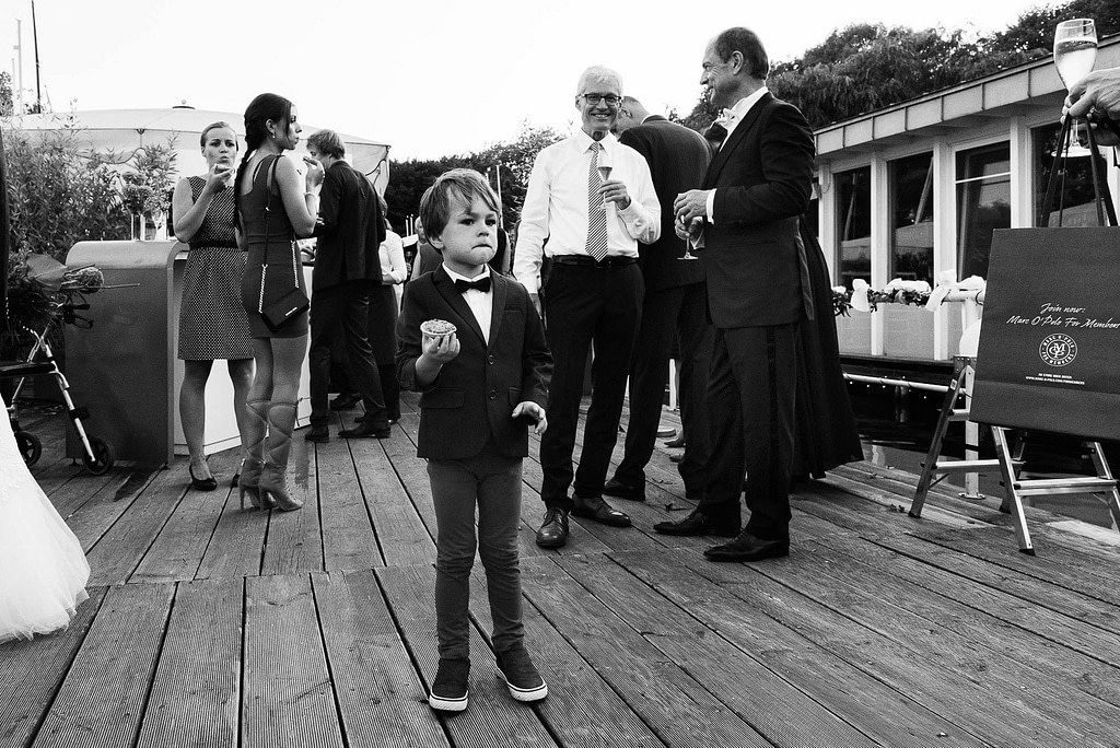 Kleiner Sohn des Hochzeitspaars hat sich einen Schokomuffin geschnappt auf dem Anleger vom Restaurante Portonovo am Alsteufer auf der Außenalster am Rothenbaum beim Hochzeitsfotograf Hamburg