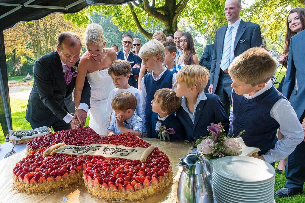 Die Hochzeitstorte wird angeschnitten im Seelemannpark bei der Eppendorfer Hochzeitskirche beim Hochzeitsfotograf Hamburg
