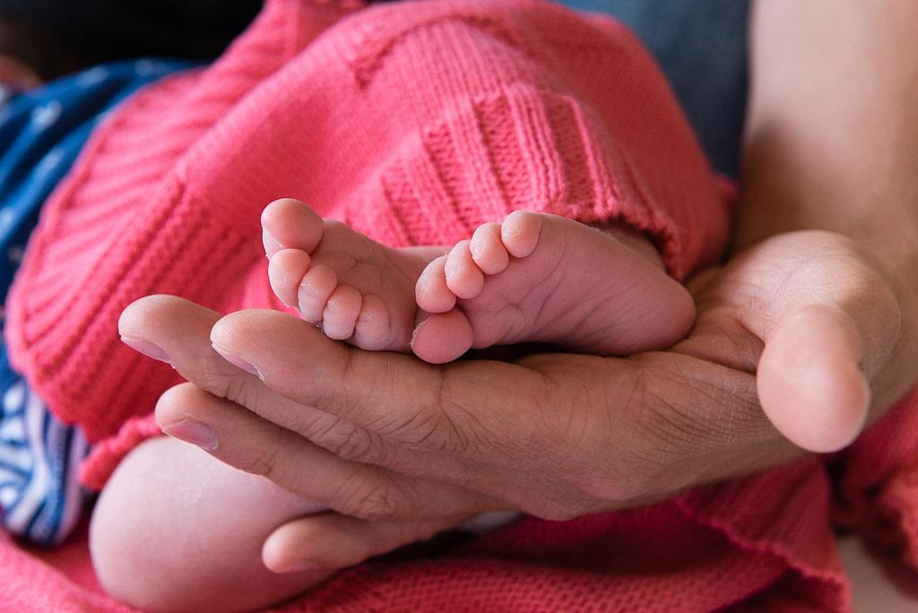 Close-up von den Babyfüssen in der Hand vom Papa beim Baby Fotoshooting zuhause in Hamburg Stellingen