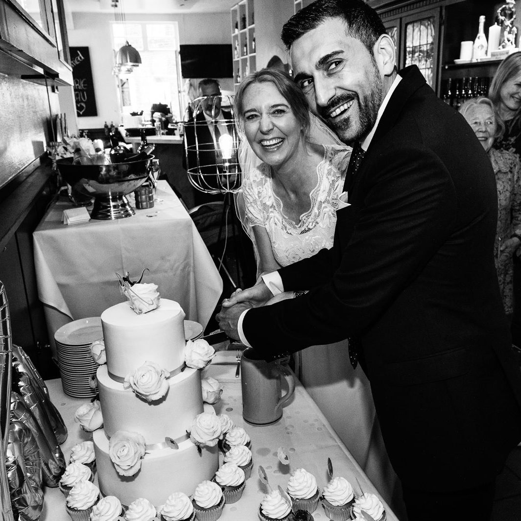 Das Hochzeitspaar schneidet gemeinsam die Hochzeitstorte bei der Hochzeitsfeier in Düsseldorf an
