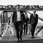 Der Bräutigam führt seine Hochzeitsgäste vom Anleger Bubendeyufer an der Elbe zur Villa im Jachthafen bei Hochzeitsfotografie Hamburg