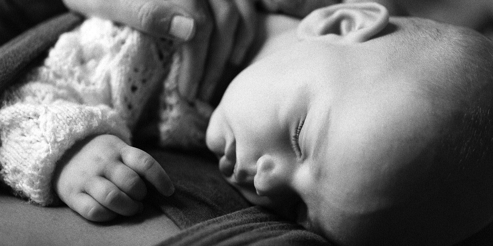 Baby Fotoshooting zuhause bei Tageslicht in Hamburg-Altona mit schlafenden Baby im Tragetuch