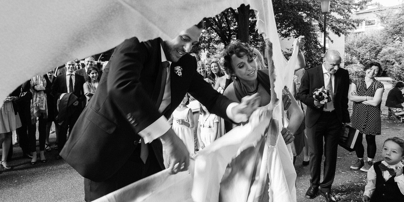 Hochzeitspaar schneidet gemeinsam ein großes Herz aus vor der Sankt Gertrud Kirche am Kuhmühlenteich in Hamburg HohenfeldeHochzeitspaar schlendert über die Kaianlagen am Australiakai im Hamburger Hafen beim Hochzeitsshooting mit dem Hochzeitsfotograf Hamburg