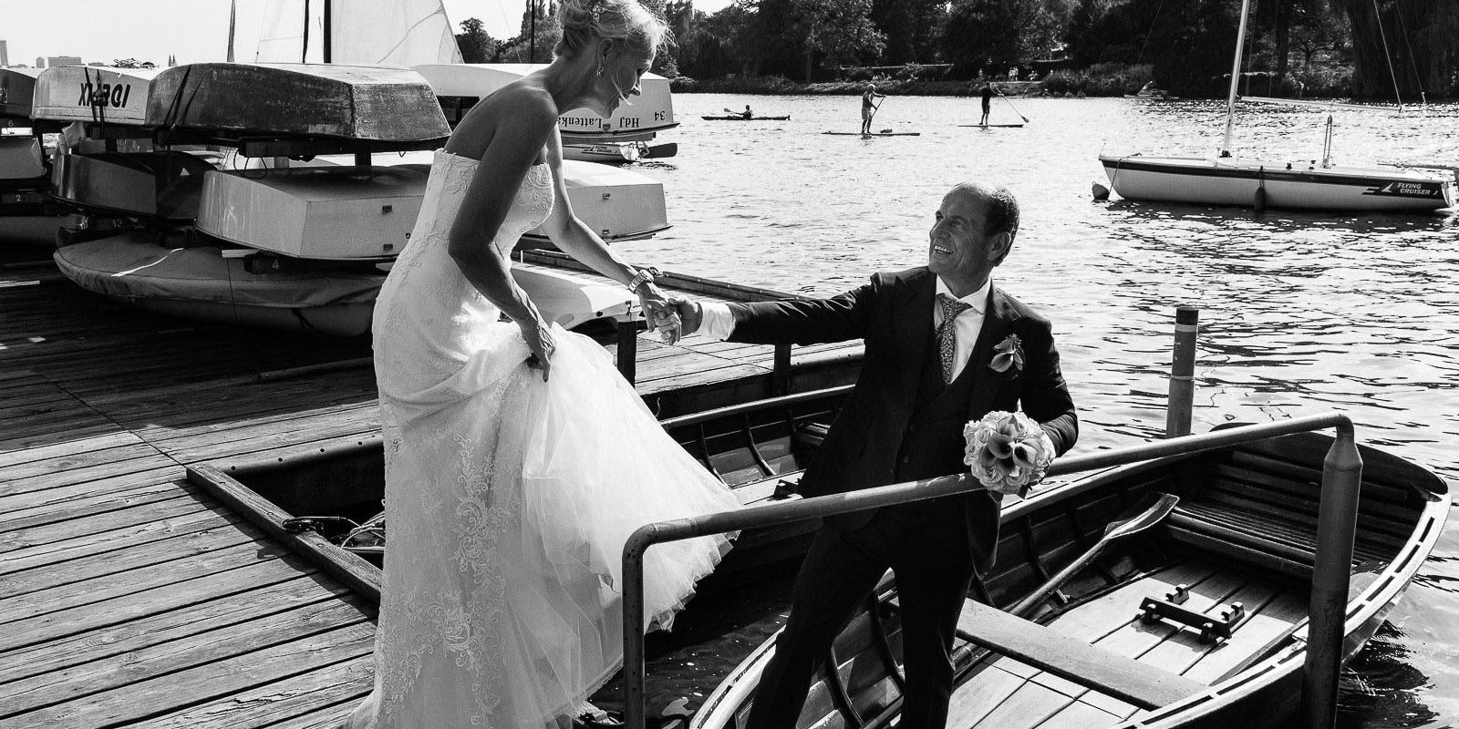 Der Bräutigam hilft seiner Braut in ein Rucerboot am Bobby Reich Bootsteg an der Außenalster in Harvestehude beim Hochzeitsfotograf Hamburg