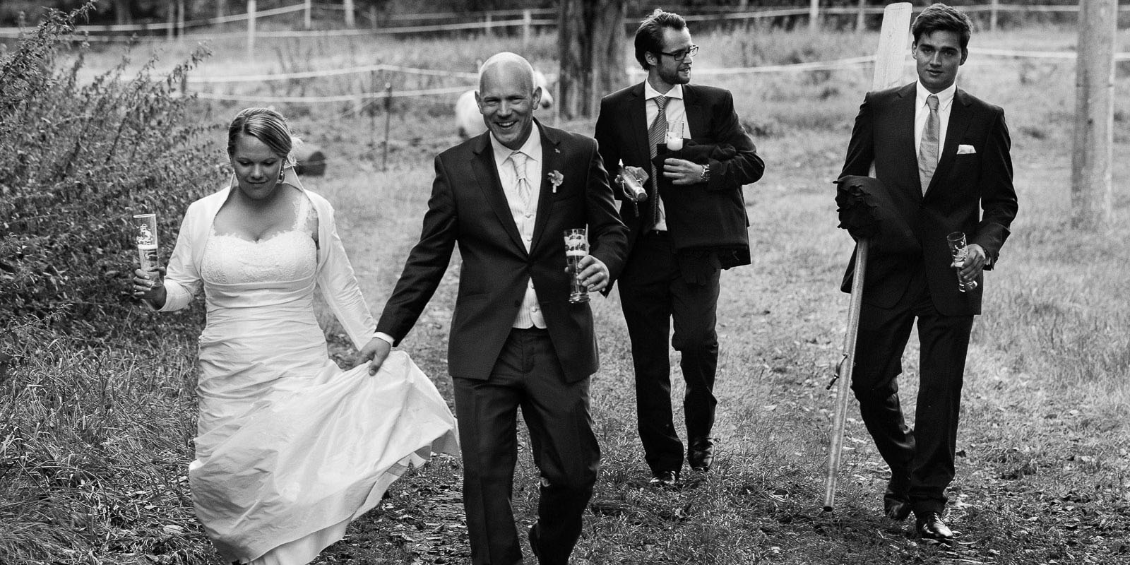 Hochzeitspaar mit Trauzeugen bei der Landhochzeit läuft gemeinsam über die Felder am Gutshof Woldzegarten in Mecklenburg Vorpommern beim Hochzeitsfotograf Hamburg