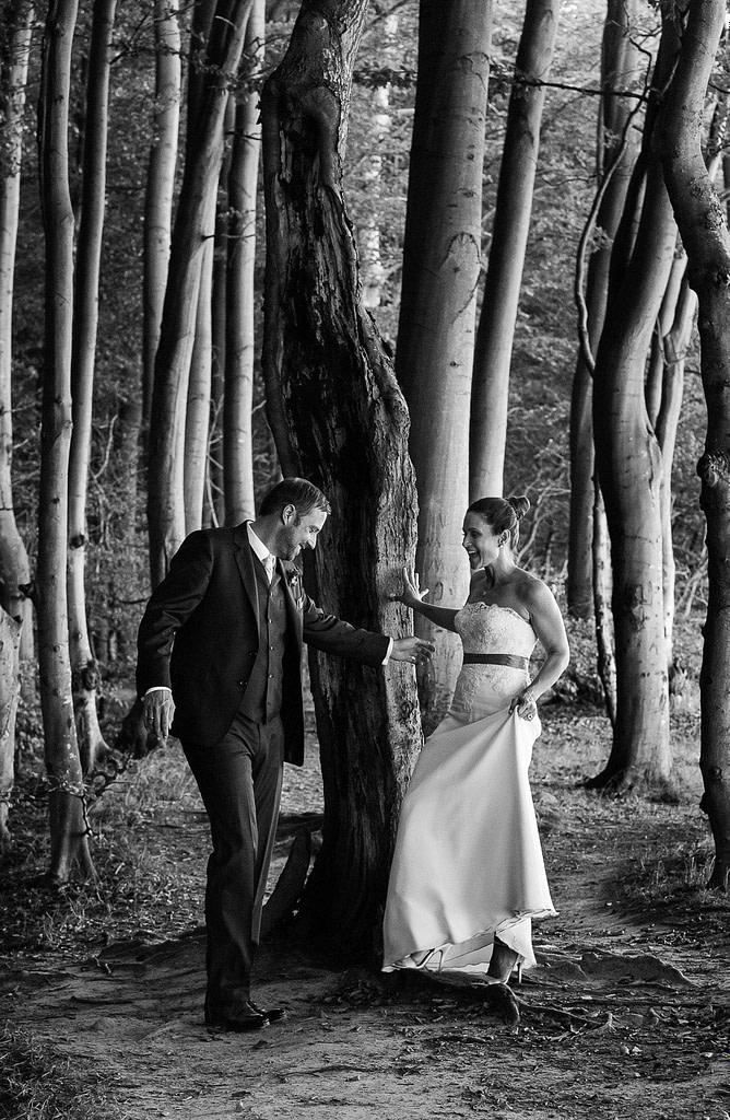 Braut und Bräutigam schlendern gemeinsam um die Bäume im märchenhaften Hochuferwald am Weissenhäuser Strand an der Ostsee beim Hochzeitsfotograf Hamburg