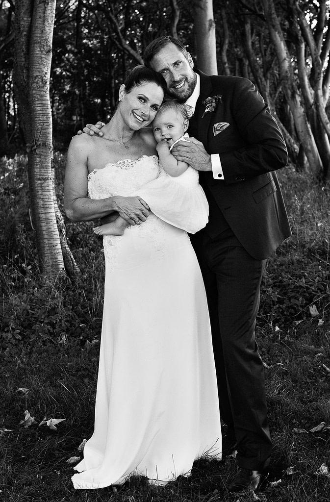 Hochzeitsportrait von Braut und Bräutigam mit kleiner Tochter im Küstenwald vom Weissenhäuser Strand an der Ostsee beim Hochzeitsfotograf Hamburg