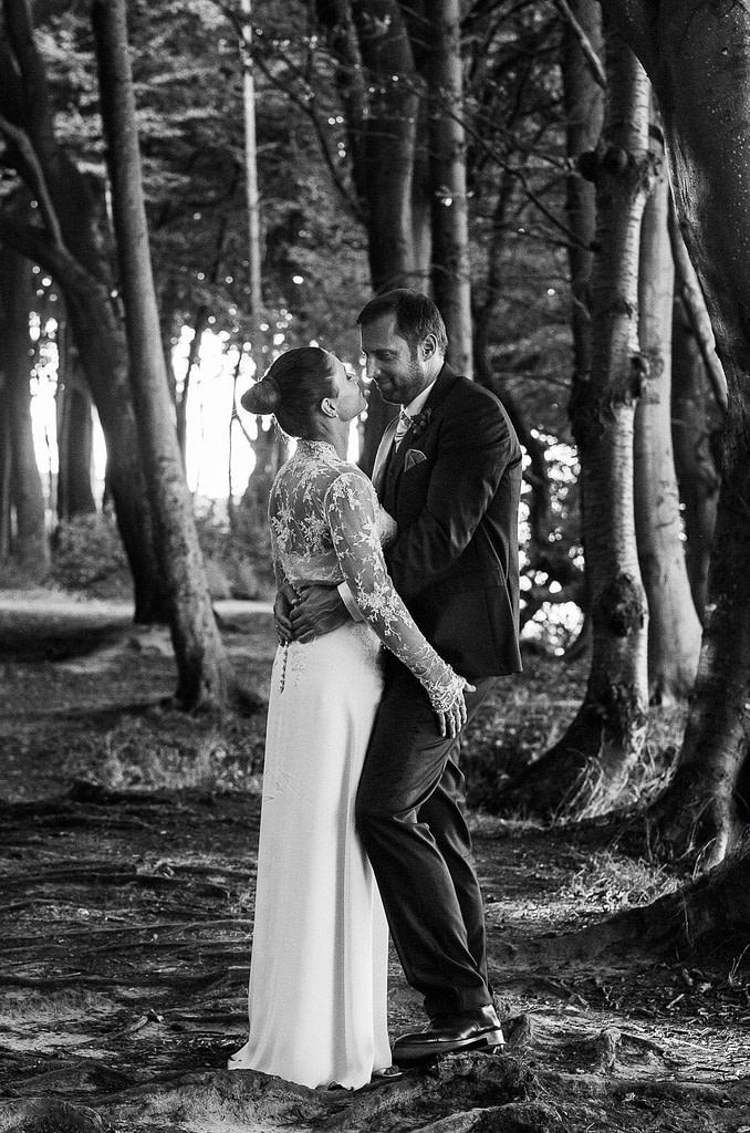 Hochzeitspaar umarmt sich bei den Brautpaarfotos am Steilufer im Märchenwald am Weissenhäuser Strand an der Ostsee beim Hochzeitsfotograf Hamburg