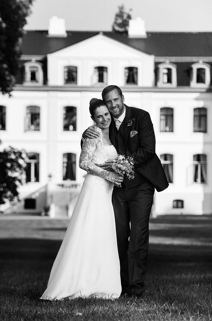 bRaut und Bräutigam posieren vor dem Schloß Weissenhaus Grand Village Resort am Weissenhäuser Strand an der Ostsee beim Hochzeitsfotograf Hamburg