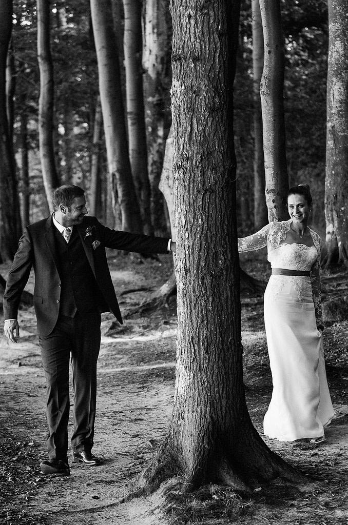 Braut und Bräutigam schlendern gemeinsam um die Bäume im märchenhaften Gespensterwald am Weissenhäuser Strand an der Ostsee beim Hochzeitsfotograf Hamburg