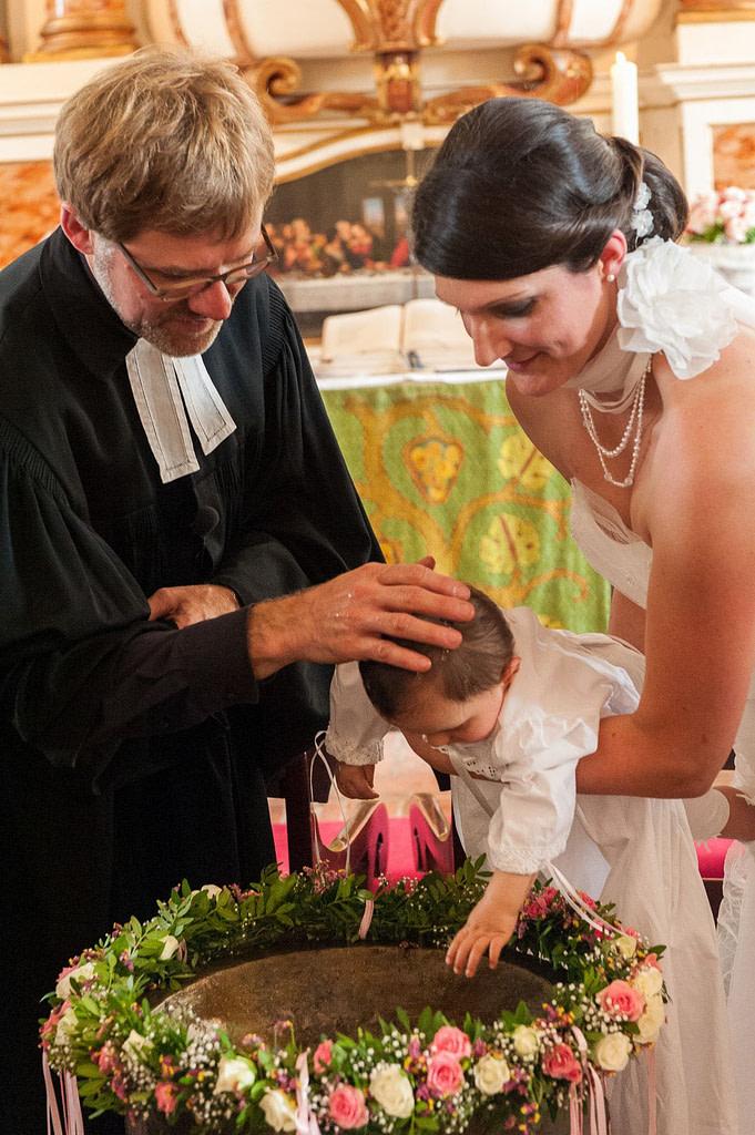 Bei der Taufe am Taufbecken erteilt der Pastor den Segen in der Hochzeitskirche in Nienstedten an der Elbe beim Hochzeitsfotograf Hamburg