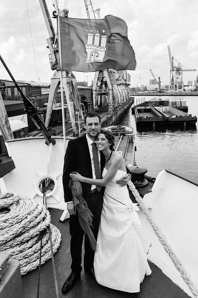 Hochzeitspaar posiert am Bug des historischen Frachters MS Bleichen vor der Flagge Hamburgs im Titanic Style Hochzeitspaar schlendert über die Kaianlagen am Australiakai im Hamburger Hafen beim Hochzeitsshooting mit dem Hochzeitsfotograf Hamburg
