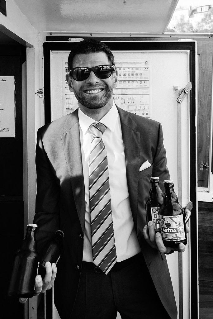 Die Hochzeitsgäste genehmigen sich auf der Fahrt mit der Barkasse schon mal ein Bier bei Hochzeitsfotografie Hamburg