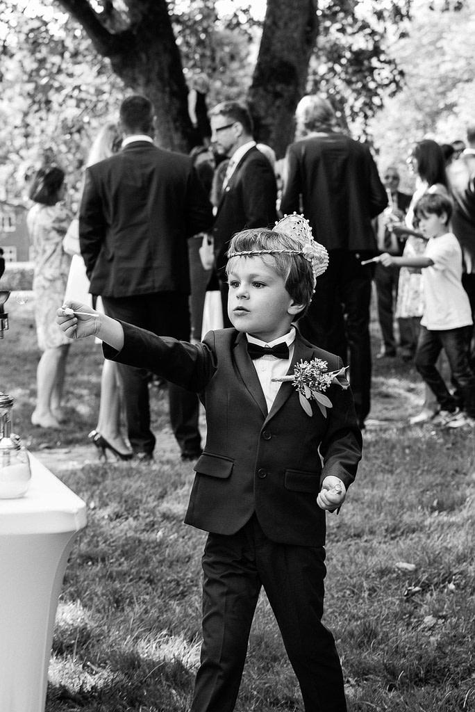 Der kleine Sohn des Hochzeitspaars im Hochzeitsanzug beim Sektempfang im Seelemannpark an der Eppendorfer Hochzeitskirche beim Hochzeitsfotograf Hamburg