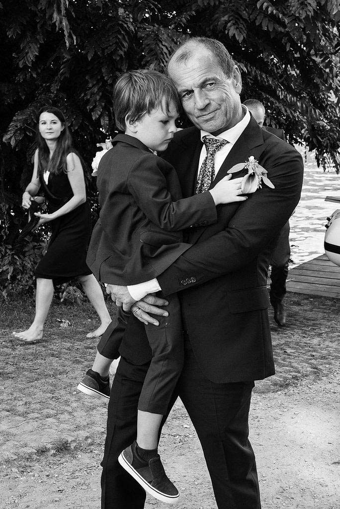 Der Bräutigam trägt seinen kleinen Sohn auf dem Arm bei den Hochzeitsfotos an der Außenalster in Harvestehude beim Hochzeitsfotograf Hamburg
