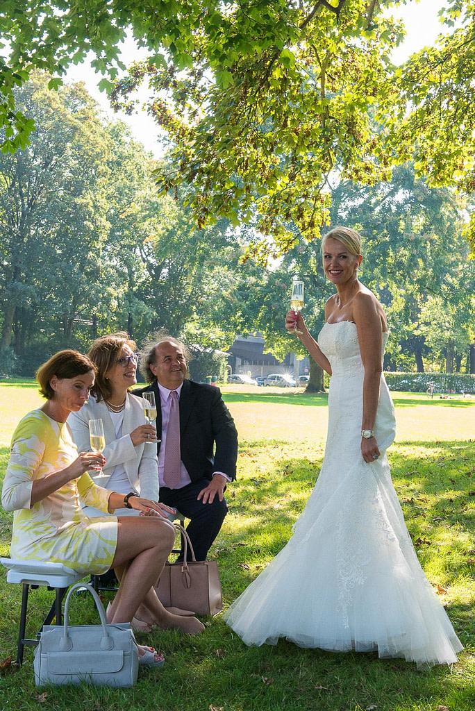 Die Braut mit ihren Hochzeitsgästen beim Sektempfang im Seelemannpark an der Eppendorfer Hochzeitskirche beim Hochzeitsfotograf Hamburg