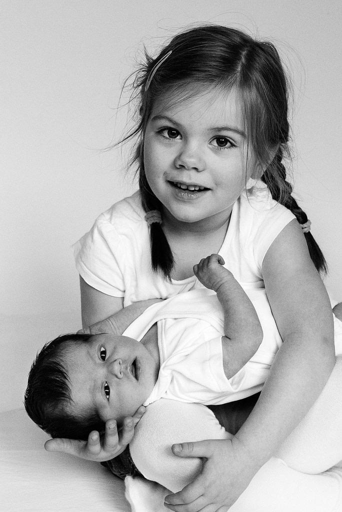 Kleines Mädchen hält ihr Schwesterchen im Arm bei der Kinderfotografie zuhause in Hamburg Barmbek