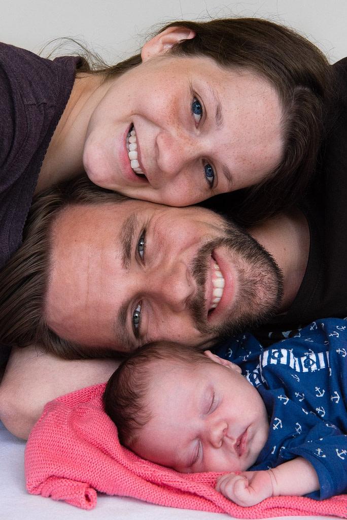 Lachende Familie mit schlafenden Baby beim Baby Fotoshooting zuhause in Hamburg Othmarschen