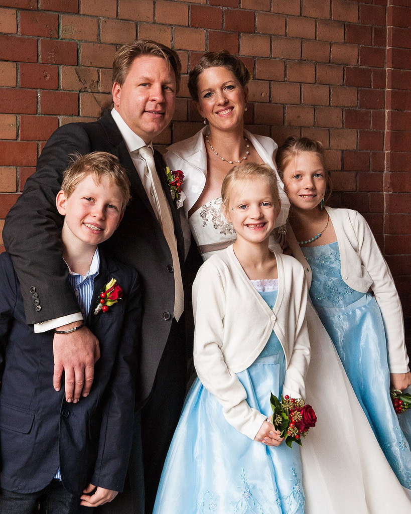 Die Hochzeitsfamilie posiert am kleinen Fleet in der Hamburger Speicherstadt. Die Hochzeitsbilder vom Hochzeitsfotograf Hamburg
