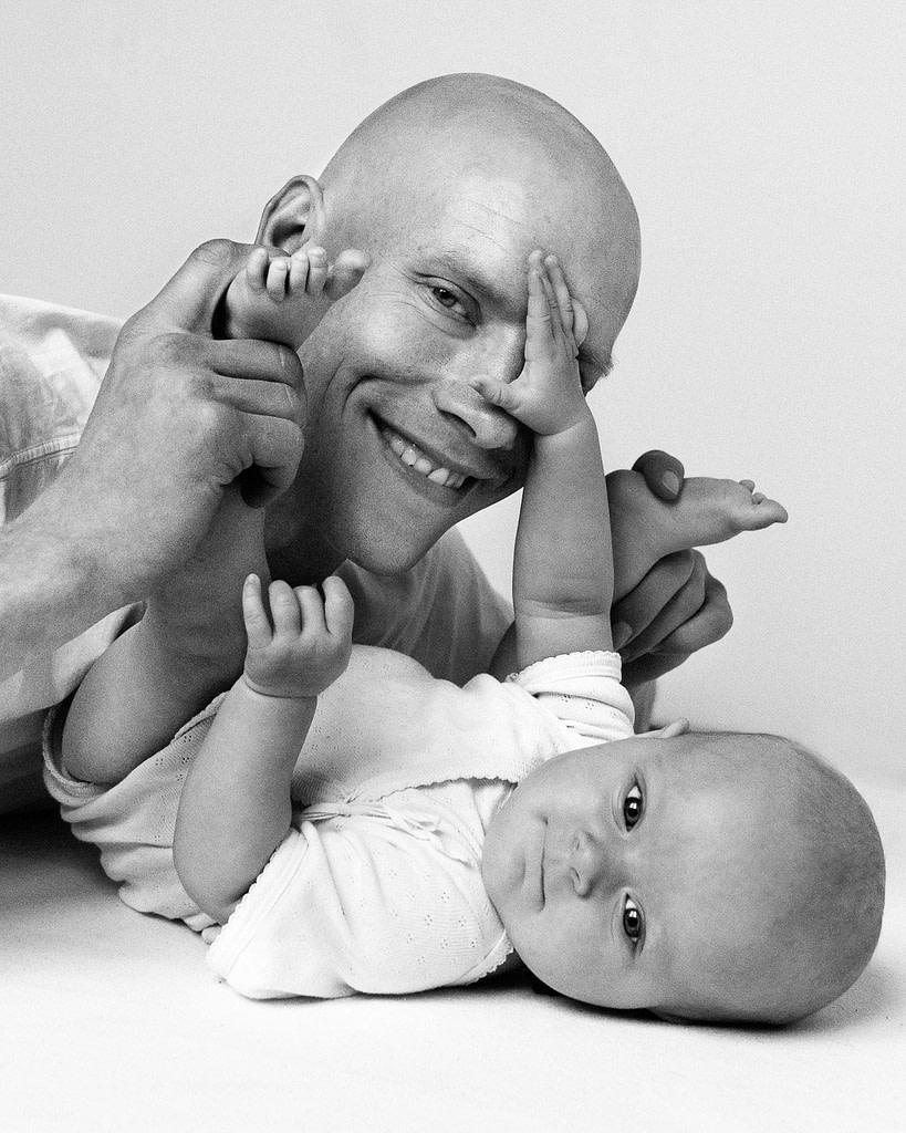 Baby greift Papa mit den Händen ins Gesicht beim Baby Fotoshooting in Hamburg Winterhude