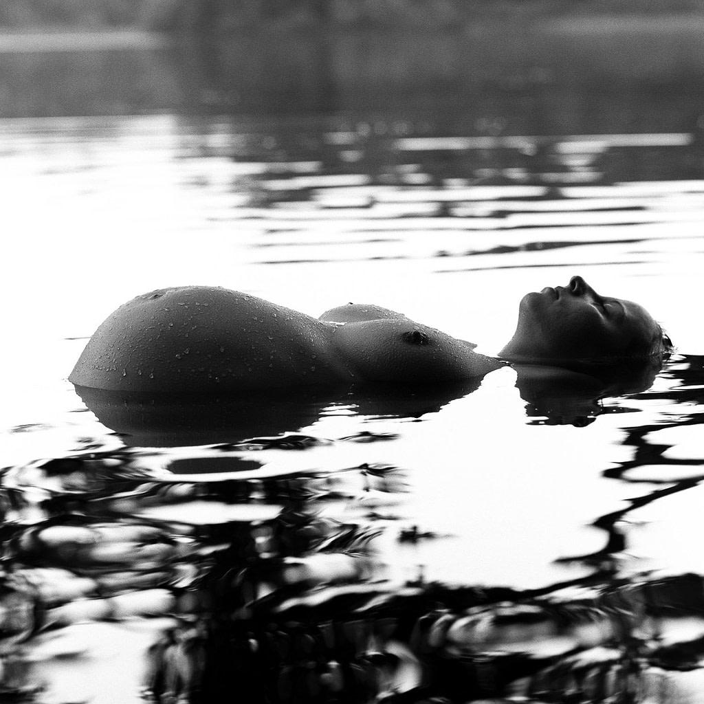 Schwangere liegt im Wasser von einem See und zeigt ihren Babybauch beim Babybauch Shooting in Hamburg draußen in der Natur