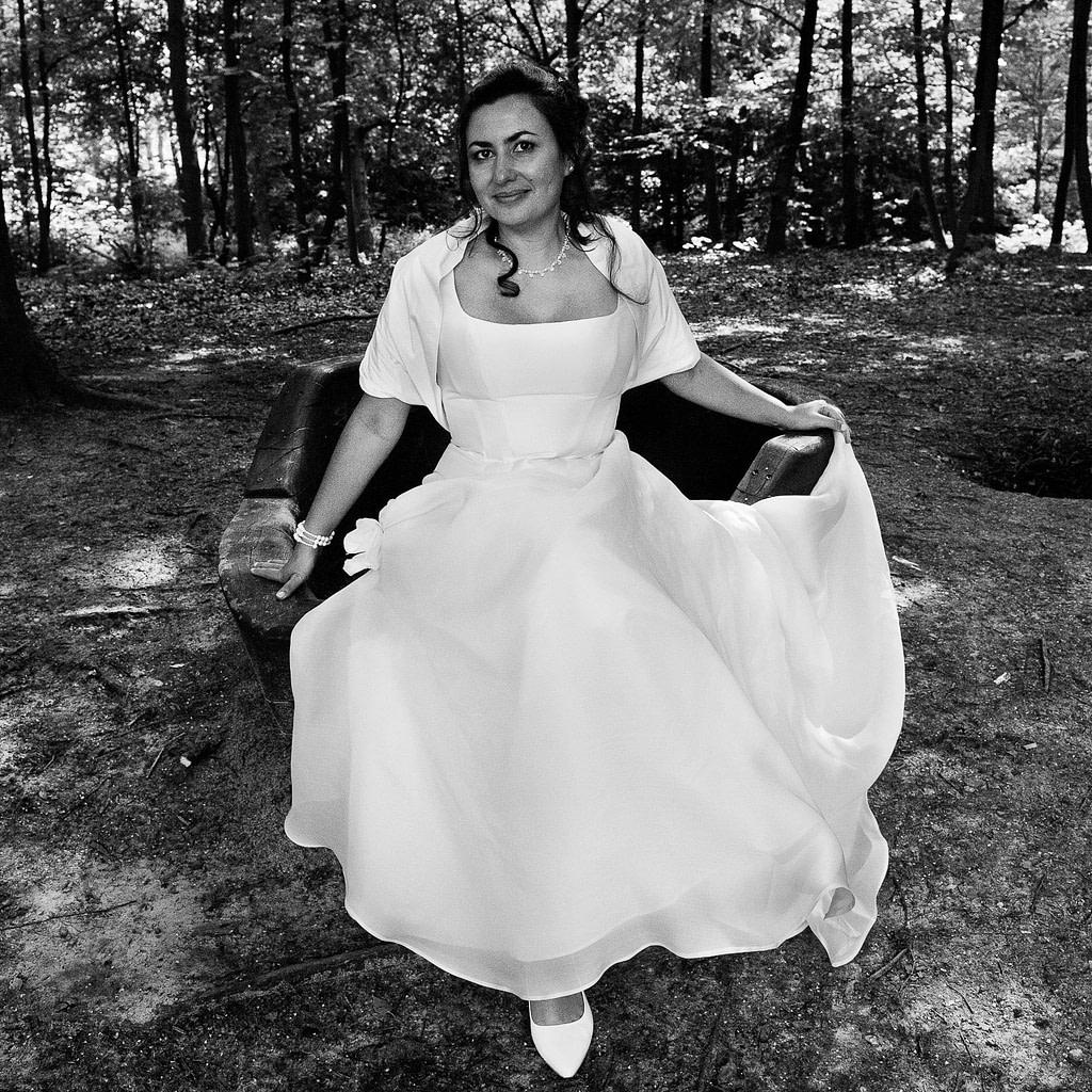 Die Braut sitzt im Wald vom Stadtpark in Hamburg Winterhude bei den Brautpaarfotos beim Hochzeitsfotograf Hamburg