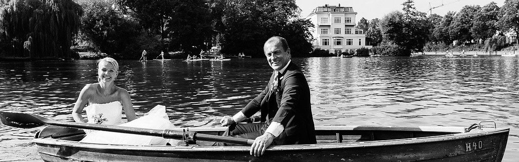 das Hochzeitspaar beim Bootsausflug im Ruderboot auf der Alster bei der Krugkoppelbrücke in Harvestehude beim Hochzeitsfotograf Hamburg
