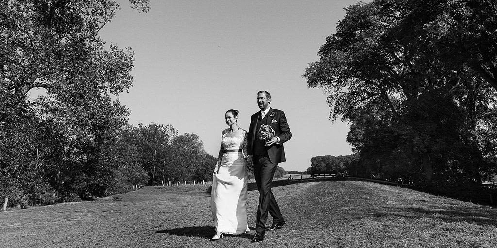 Das Hochzeitspaar schreitet Hand in Hand über den Deich auf dem Weg zum Sektempfang am Bootshaus vom Schloß Weissenhaus Grand Village Resort am Ostseestrand beim Hochzeitsfotograf Hamburg