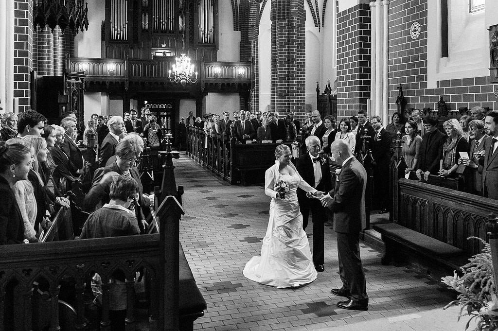 Brautvater übergibt die Braut dem Bräutigam vor der Trauung in der Sankt Marien Kirche in Röbel an der Müritz in Mecklenburg Vorpommern beim Hochzeitsfotograf Landhochzeit Hamburg