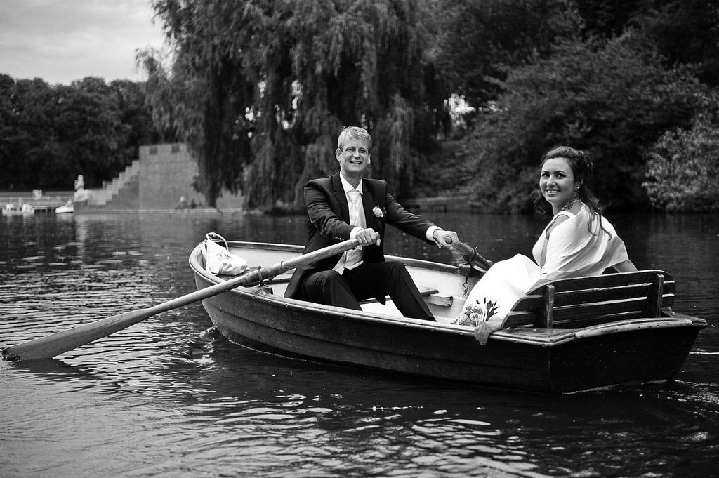 Lachendes Hochzeitspaar im romantischen Ruderboot auf dem Stadtparksee in Hamburg Winterhude bei den Brautpaarfotos beim Hochzeitsfotograf Hamburg