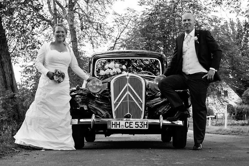 Hochzeitspaar posiert vo dem Hochzeitsauto Citroen Gangsterlimosine CV11 bei der Landhochzeit in Röbel an der Müritz in Mecklenburg Vorpommern beim Hochzeitsfotograf Landhochzeit Hamburg