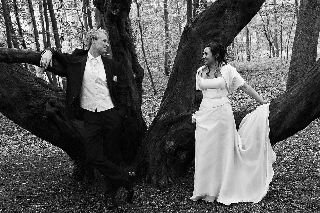 Hochzeitspaar posiert vor großen alten Baum im Hamburger Stadtpark in Hamburg Winterhude bei den Brautpaarfotos beim Hochzeitsfotograf Hamburg