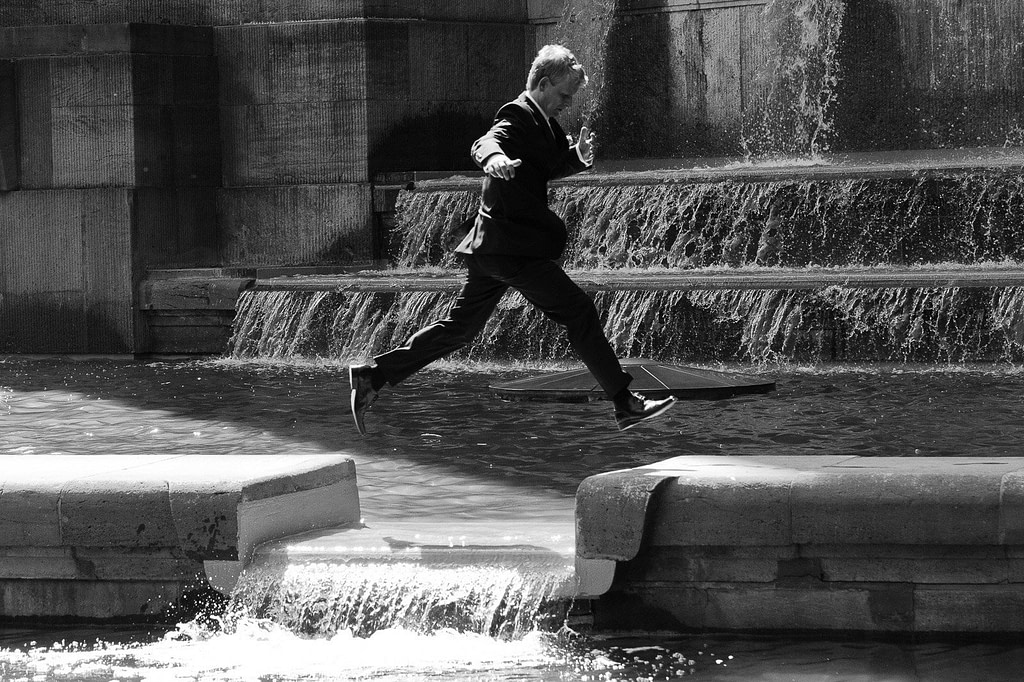 Bräutigam springt über das Wasser am Springbrunnen vor dem Planetarium im Hamburger Stadtpark bei den Brautpaarfotos beim Hochzeitsfotograf Hamburg