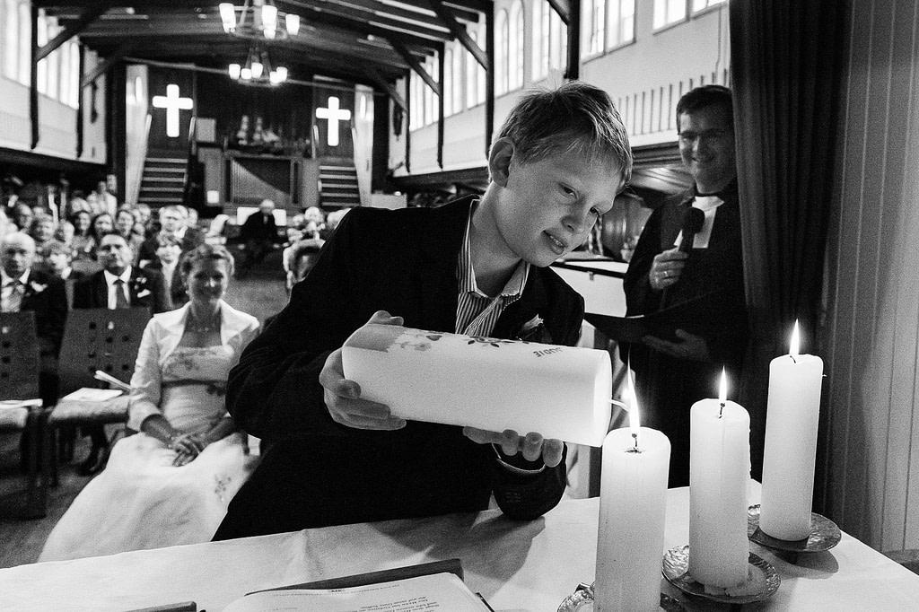 Der Sohn zündet die Taufkerze am Altar in der Flußschifferkirche an. Die Hochzeitsbilder vom Hochzeitsfotograf Hamburg