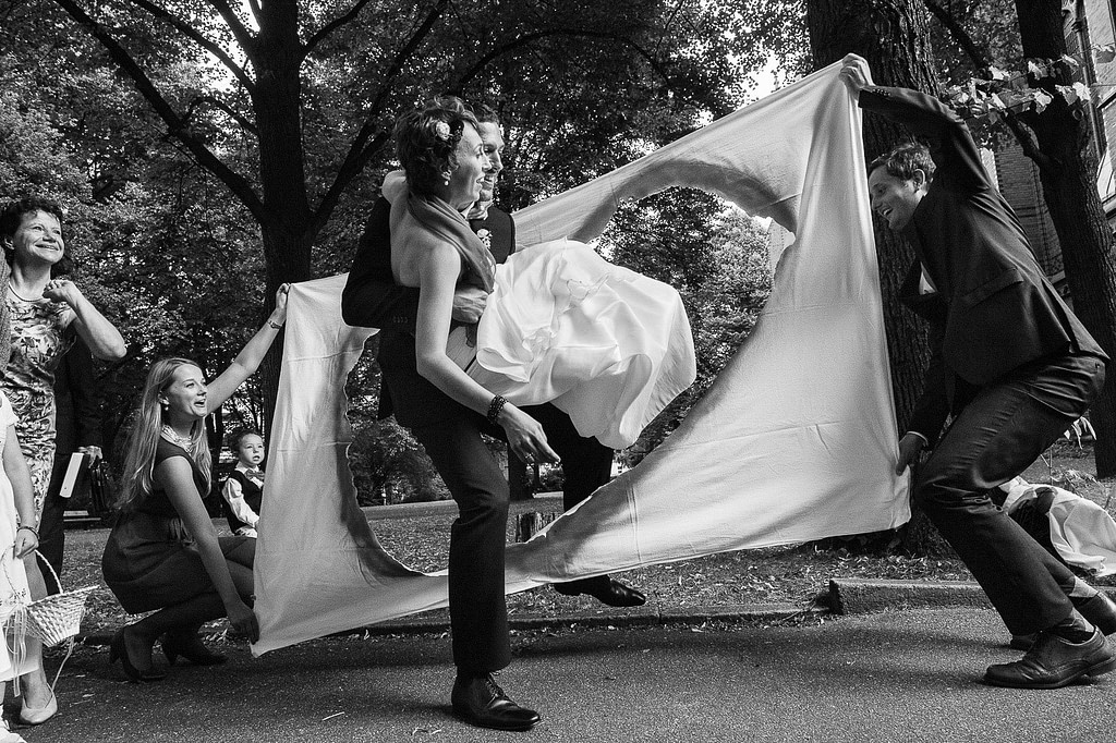 Bräutigam trägt seine Braut durch ein großes Herz vor der Sankt Gertrud Kirche am Kuhmühlenteich in Hamburg HohenfeldeHochzeitspaar schlendert über die Kaianlagen am Australiakai im Hamburger Hafen beim Hochzeitsshooting mit dem Hochzeitsfotograf Hamburg