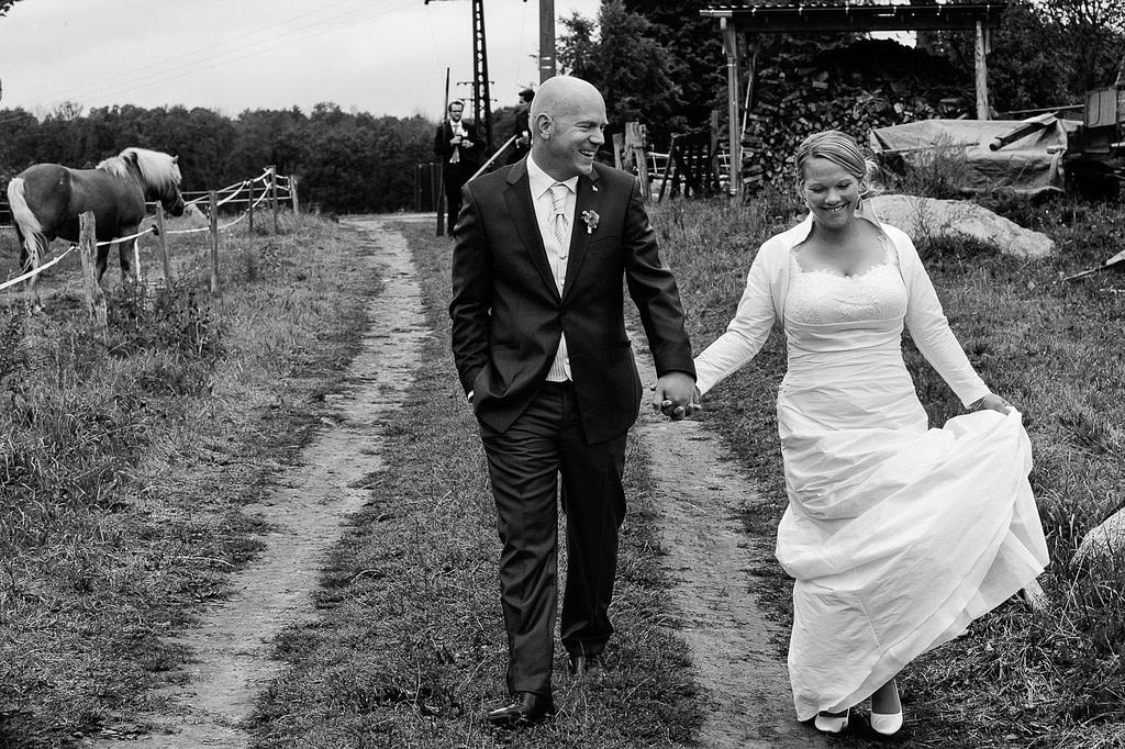 Hochzeitspaar bei der Landhochzeit läuft gemeinsam über die Felder am Gutshof Woldzegarten in Mecklenburg Vorpommern beim Hochzeitsfotograf Landhochzeit Hamburg