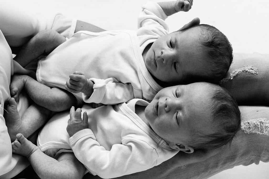 Zwillinge nebeneinander auf den Beinen der Mutter liegend beim Baby Fotoshooting in Hamburg Barmbek