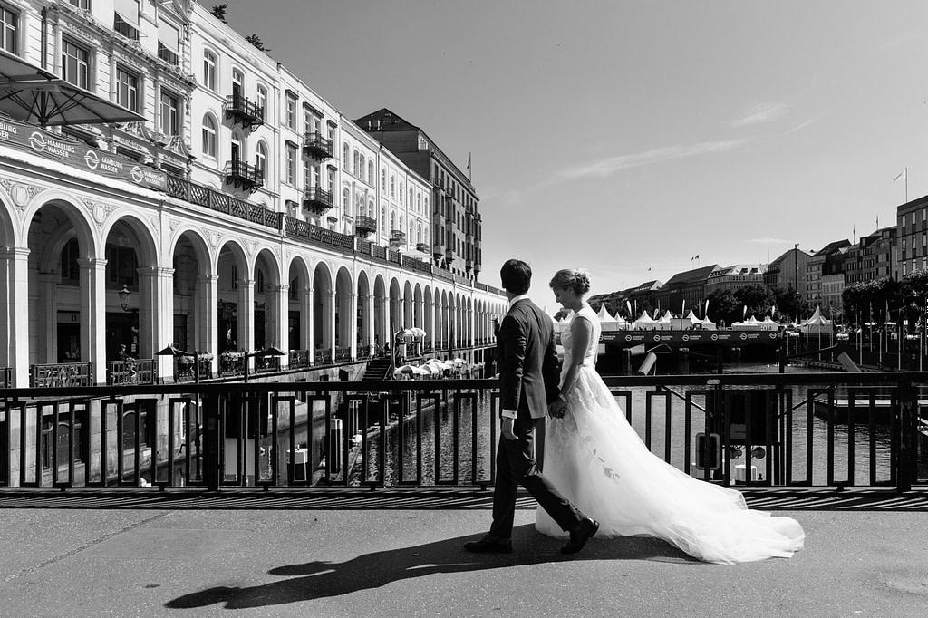 Das Hochzeitspaar flaniert an den Alsterarkaden in der Hamburger Innenstadt beim Hochzeitsfotograf Hamburg