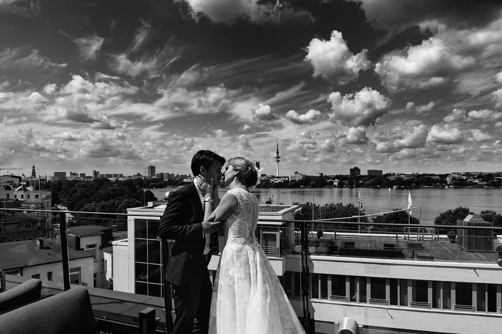 Hochzeitskuß mit Panorama Blick über die Aussenalster von der Dachtersse vom Hotel The George in Sankt Georg beim Hochzeitsfotograf Hamburg