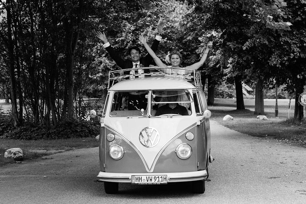 Das Brautpaar winkt aus dem Hochzeitsauto VW Bus T1 am Goldschätzchen der Koch Fabrik auf dem Golf Park Peiner Hof in Priesdorf beim Hochzeitsfotograf Hamburg