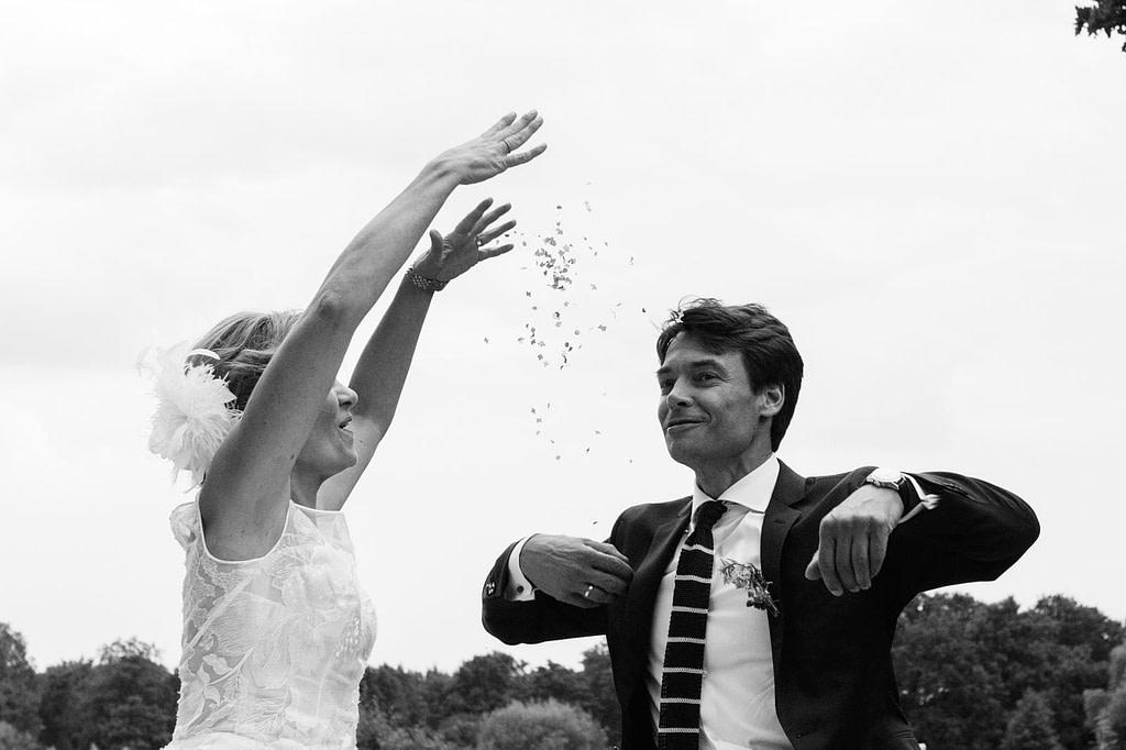 Das Hochzeitspaar wirft Konfetti am Goldschätzchen der Koch Fabrik auf dem Golf Park Peiner Hof in Priesdorf beim Hochzeitsfotograf Hamburg