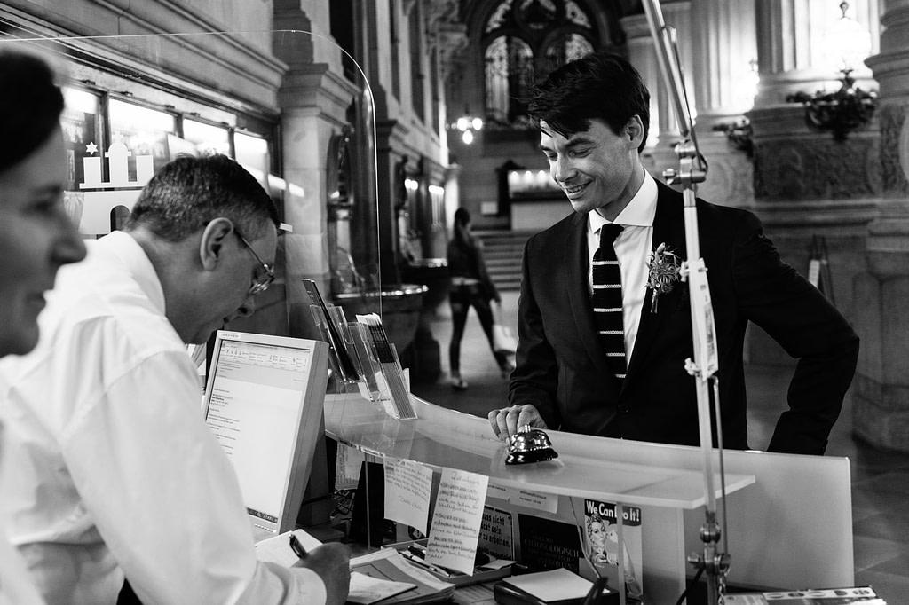 Der Bräutigam entrichtet an der Rezeption der Empfangshalle vom Hamburger Rathaus die Gebühren für die Trauung im Phönixsaal beim Hochzeitsfotograf Hamburg