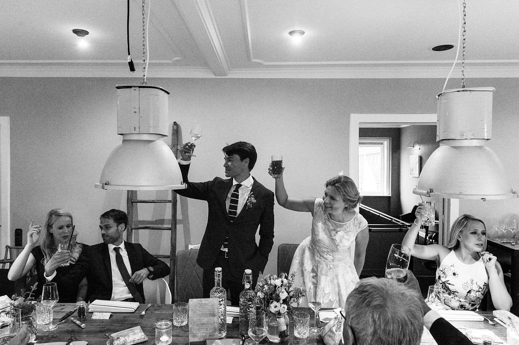 Das Hochzeitspaar und die Hochzeitsgäste stoßen auf die Hochzeitsfeier an im Goldschätzchen der Koch Fabrik auf dem Golf Park Peiner Hof in Priesdorf beim Hochzeitsfotograf Hamburg