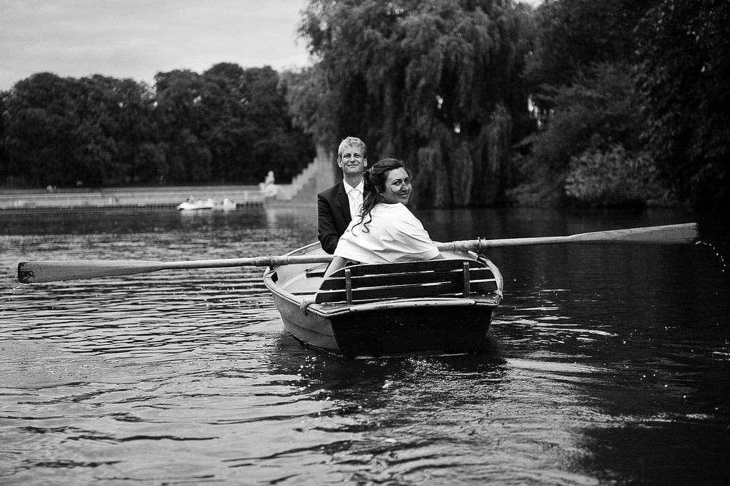 Freudiges Hochzeitspaar im romantischen Ruderboot auf dem Stadtparksee in Hamburg Winterhude bei den Brautpaarfotos beim Hochzeitsfotograf Hamburg