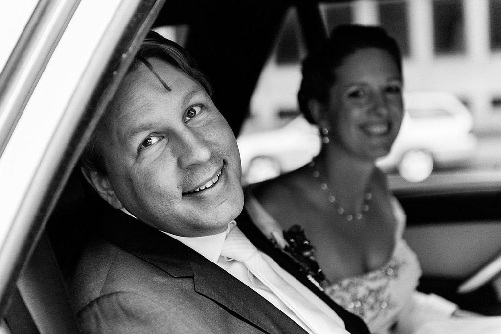 Glückliches Hochzeitspaar nach der Trauung im Hochzeitsauto. Die Hochzeitsbilder vom Hochzeitsfotograf Hamburg