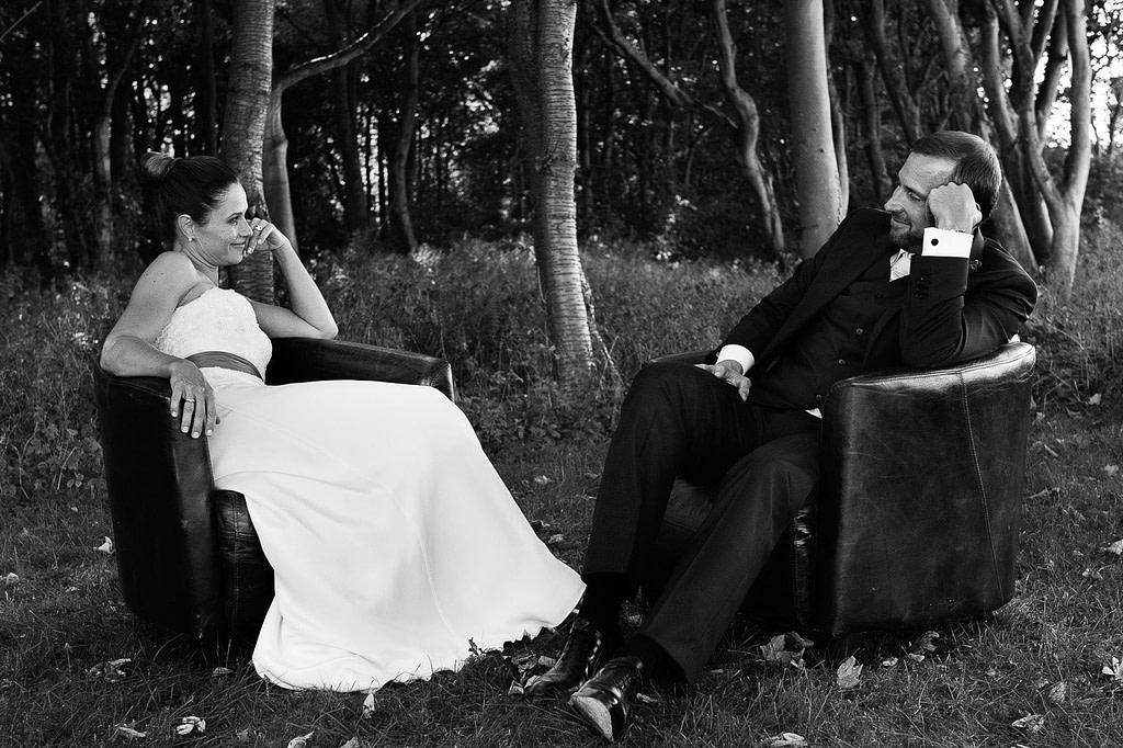 Hochzeitspaar flirtet in Vintage Ledersesseln im Küstenwald am Weissenhäuser Strand an der Ostsee beim Hochzeitsfotograf Hamburg