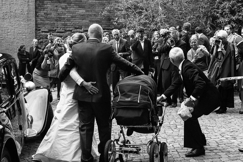 Hochzeitspaar posiert vor seinen Hochzeitsgästen nach der Trauung für das Hochzeitsfoto vor der Sankt Marien Kirche in Röbel an der Müritz in Mecklenburg Vorpommern beim Hochzeitsfotograf Landhochzeit Hamburg